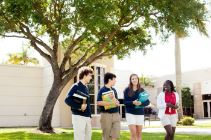 Students walking out of campus building with books